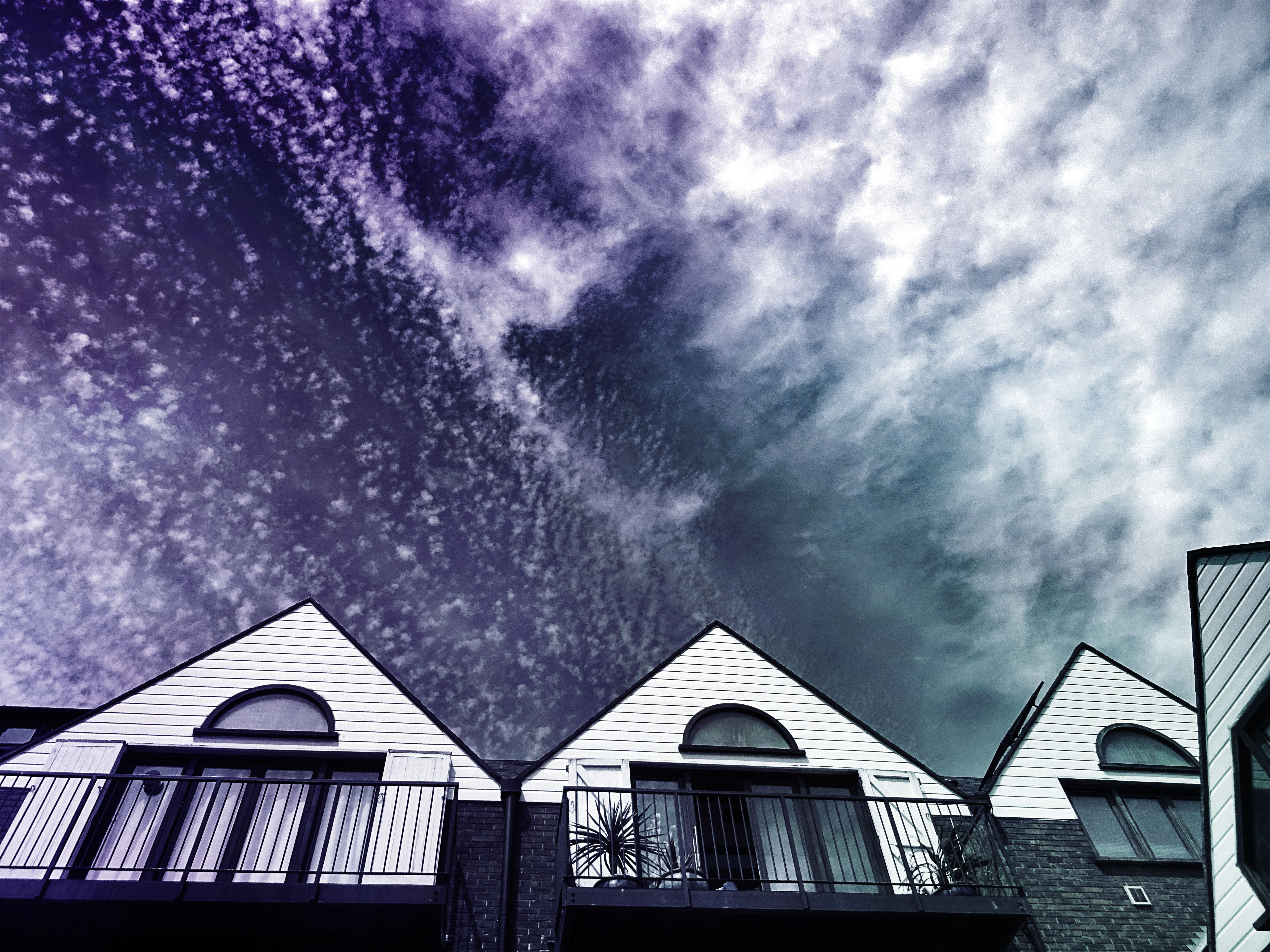 White Painted Houses Under Cloudy Sky