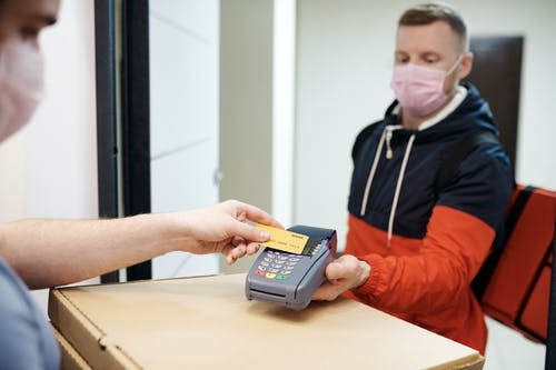 Person Paying for Food Delivery with a Credit Card