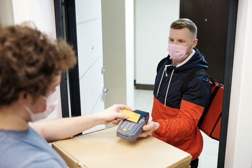 Person Wearing a Face Mask Paying for a Delivery