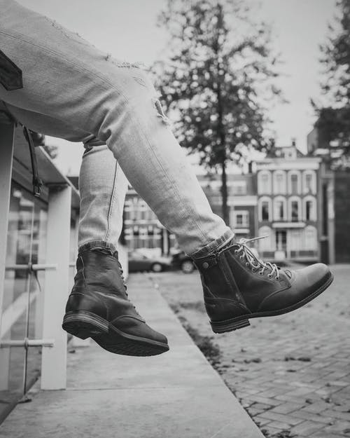 Crop person in denim trousers and dark boots resting on bench in city with pavement and buildings