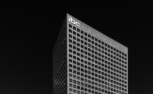 Black and white corner of contemporary multi storey office building on black background