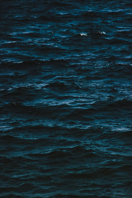 Abstract background of dark rippling surface of endless sea in rich ultramarine color