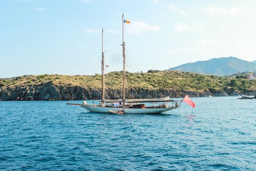 Light blue sky with clouds above long passenger sailboat with roof near rocky coast covered with grass