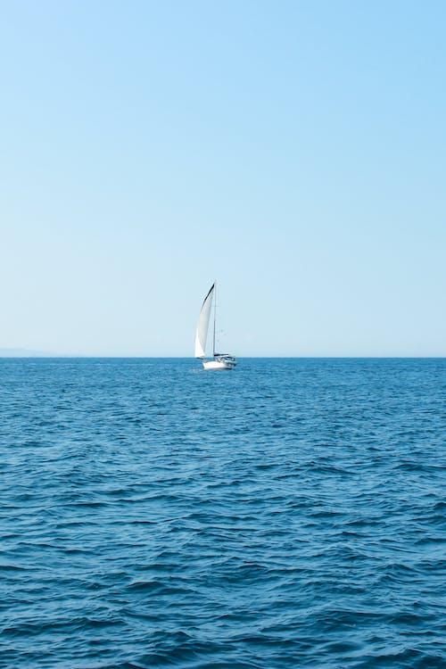 Sailboat in vibrant blue high sea