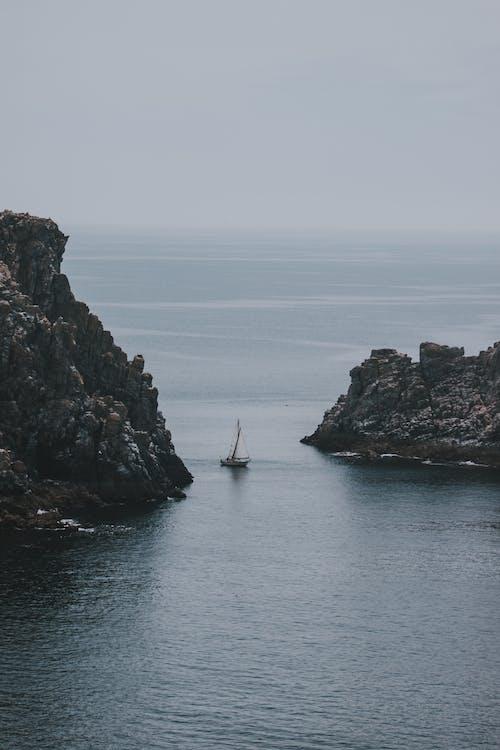 Sailboat between steep rocks in ocean