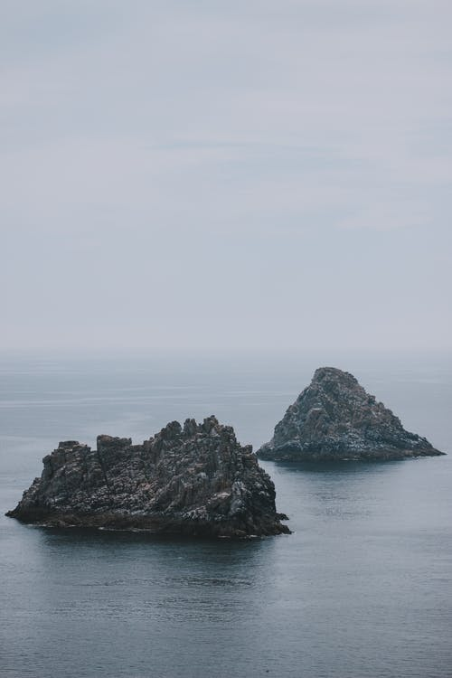 Scenic seascape with rough rocks located in calm water of sea on cloudy day