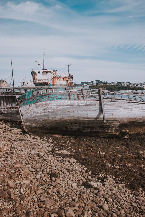 Shabby wooden fishing boat forgotten on seashore on sunny day in old port