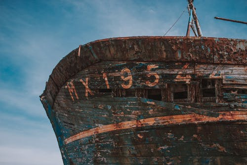 Low angle of detail of shabby abandoned ship located on shore against blue sky