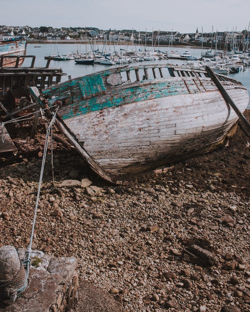 Broken boat on beach in port