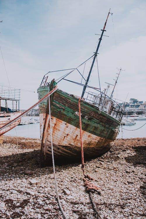 Rusty ship on seashore in harbor