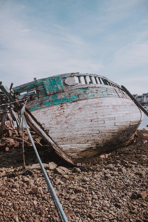Shabby boat on seashore on sunny day