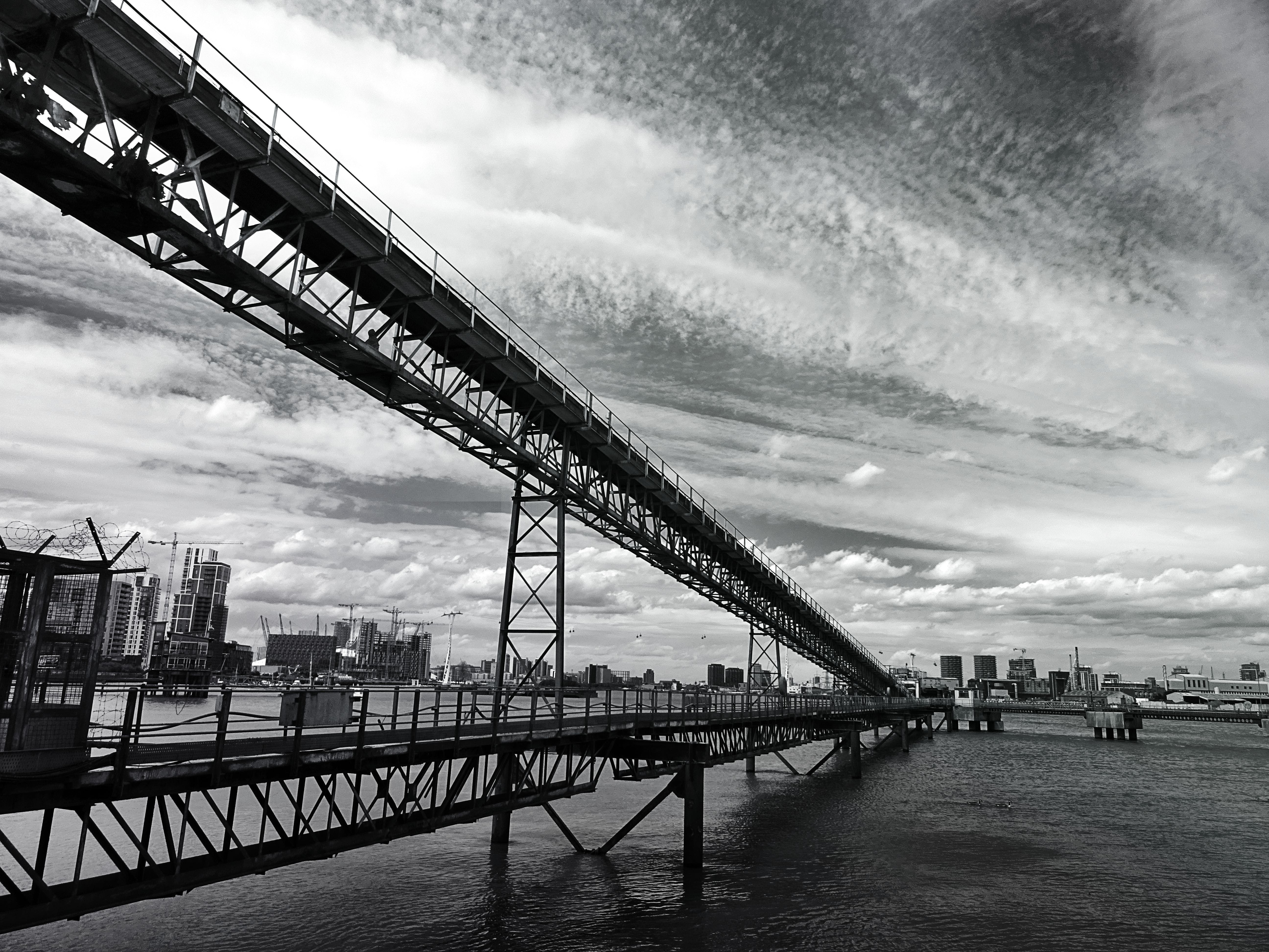Grayscale Photo of Bridge Surrounded by Body of Water