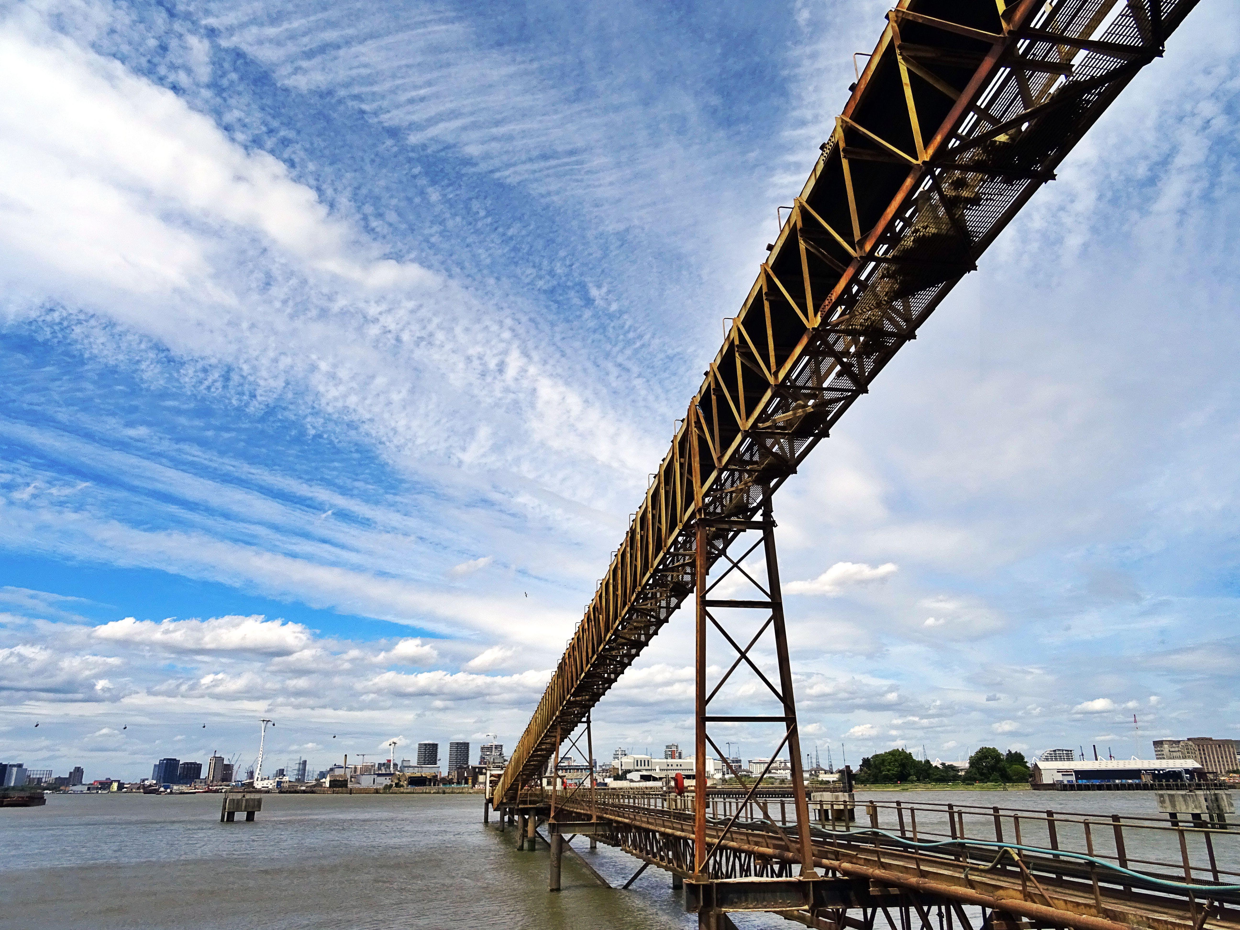 Brown Steel Bridge Under Cloudy Sky