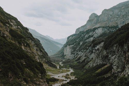 Mountainous terrain under gray cloudy sky