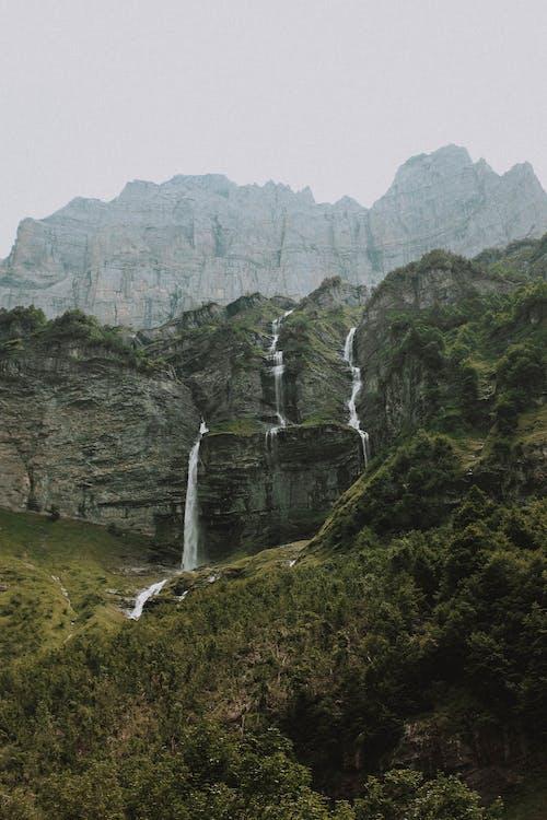 Неровная зеленая местность возле скалистой горы