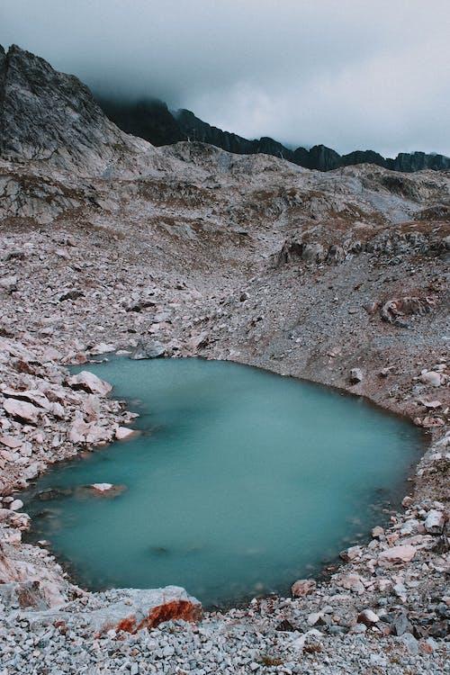 Blue lake on rocky terrain under gray sky