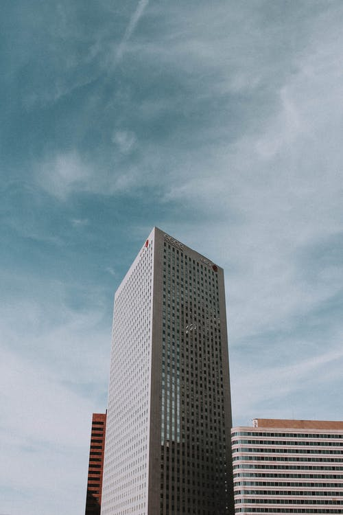 Contemporary buildings in financial district against cloudy blue sky