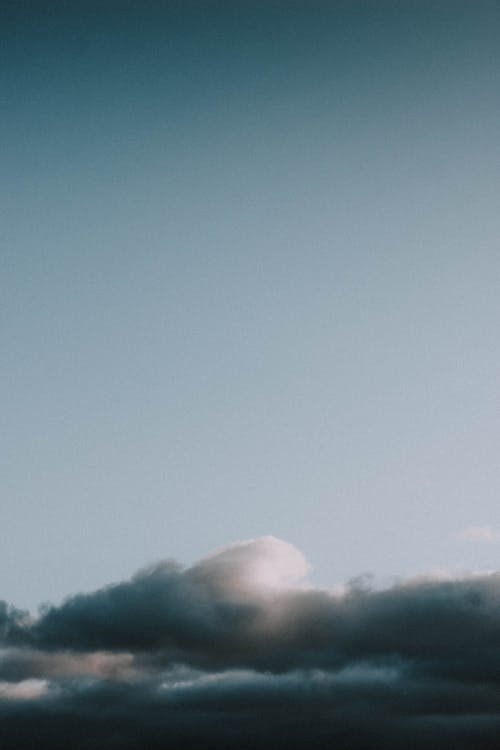 Sun rays shining through clouds in blue sky
