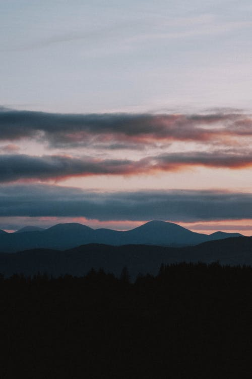 Picturesque scenery of high mountains and trees silhouettes against cloudy sky at sundown
