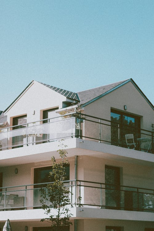 Low angle corner of modern residential house with glass balconies and sharp roof against cloudless blue sky