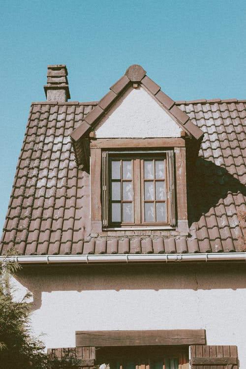 Old fashioned house with mansard window on sunny day