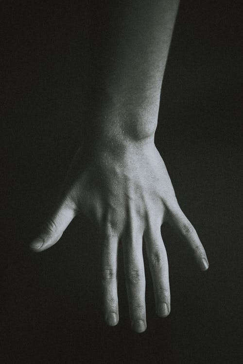 From above of black and white hand of crop anonymous person against dark background