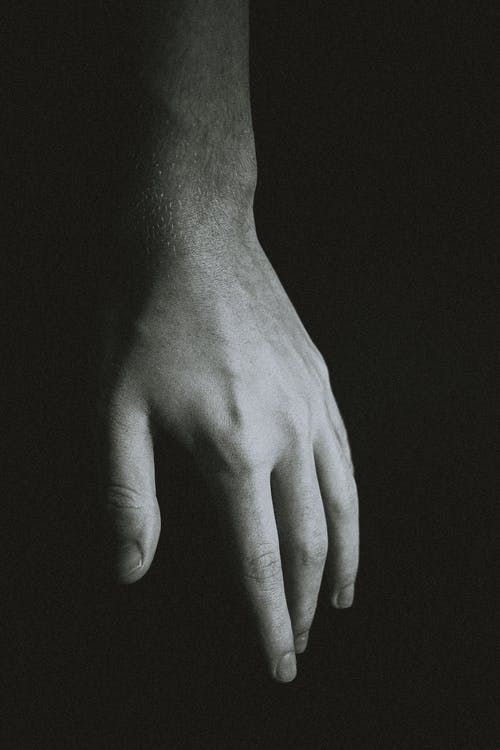 Hand of crop anonymous man against black background