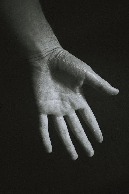 Black and white of crop faceless person giving helping hand against dark background