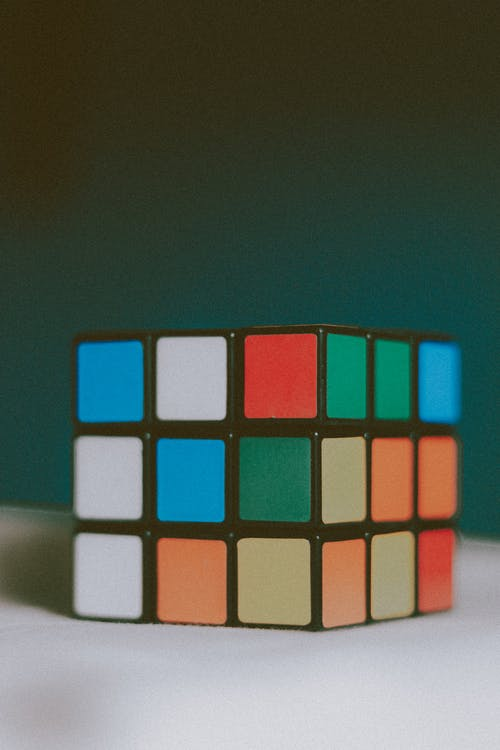 Unsolved three dimensional magic cube with multicolored stickers placed on white table against dark wall