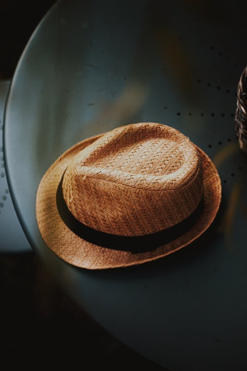 Trendy straw hat placed on black round table