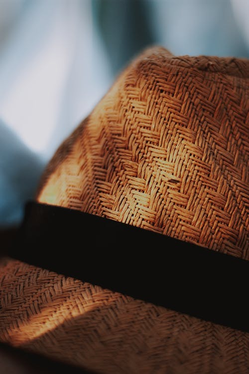 Detail of weaved straw hat with black ribbon
