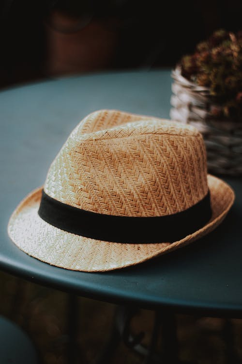 Trendy wicker straw hat placed on table in cafeteria