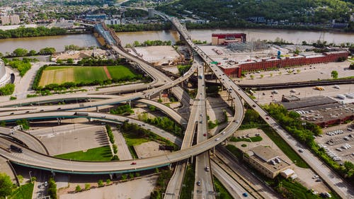 Drone view of modern cars riding through junction above greenery and broad river