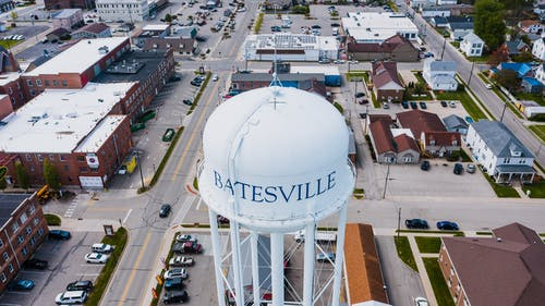 From above of white tall contemporary water tower surrounded by roads and buildings