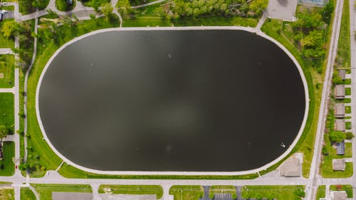 Drone view of black oval reservoir in park surrounded by greenery and settlement in daylight