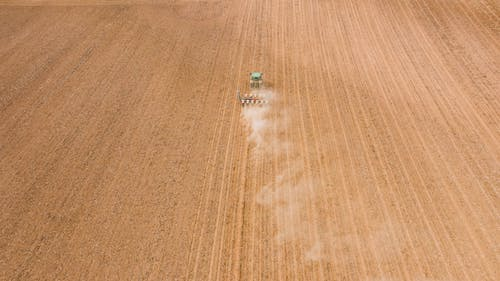 Contemporary tractor leaving long traces and smoke while plowing brown plantation in daylight