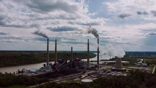 Air pollution by smoke coming out of factory chimneys located near river against cloudy sky on summer day