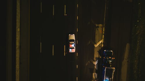 From above of police cruiser with flashing lights driving on asphalt road along dimly illuminated street at night