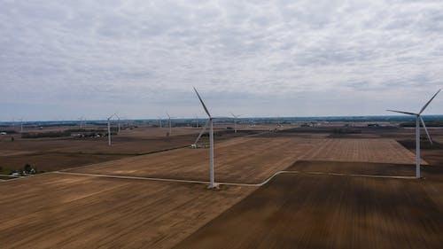 Wind generators in field under cloudy sky