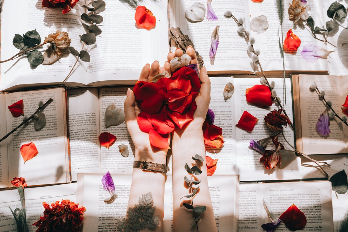 Scents That Will Boost Your Productivity - woman with bright flower petals on books