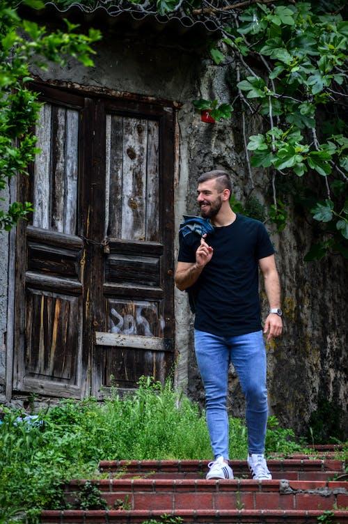 Man in Black Crew Neck T-shirt and Blue Denim Jeans Standing Beside Brown Wooden Door
