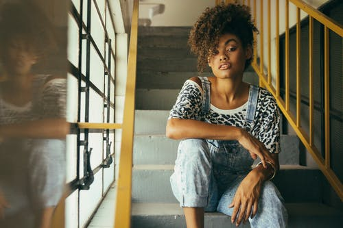 Stylish African American woman resting on stairs in building