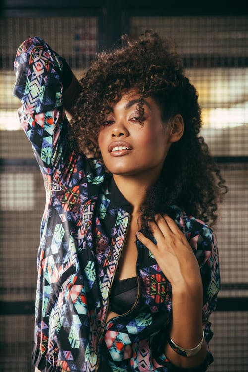 Young feminine black female in stylish wear with curly hair standing with raised arm while looking at camera