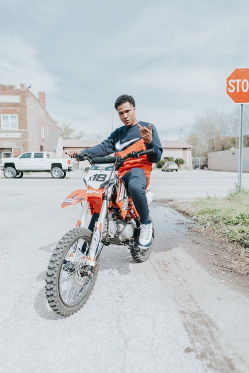 Man in Black and Orange Jacket Riding Red and Black Motorcycle