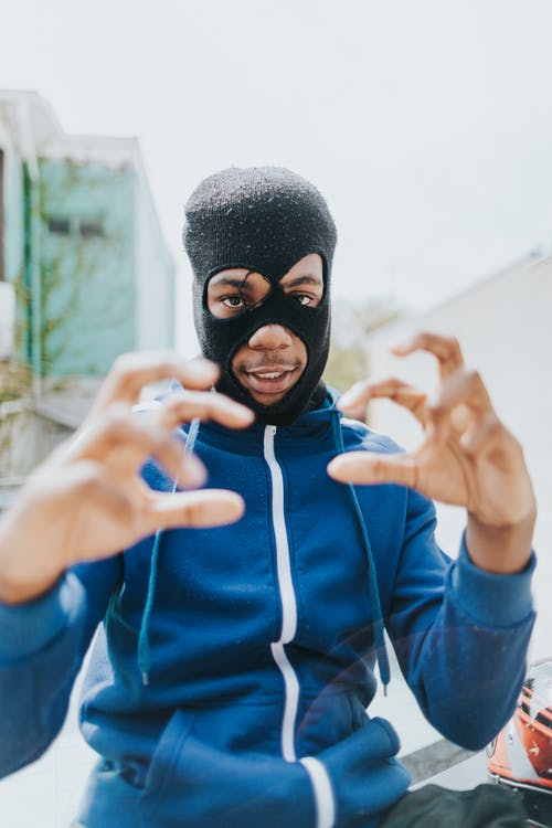 Man in Blue and Black Nike Zip Up Hoodie Covering His Face With His Hand
