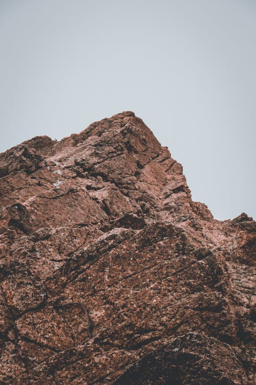 From below of dry brown mount with uneven bristly surface and pointed peak under white sky