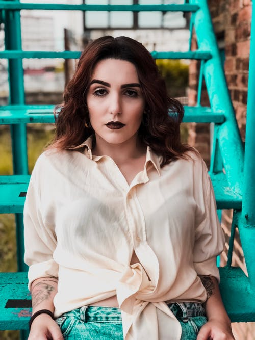 Trendy ethnic hipster woman with dark makeup on staircase