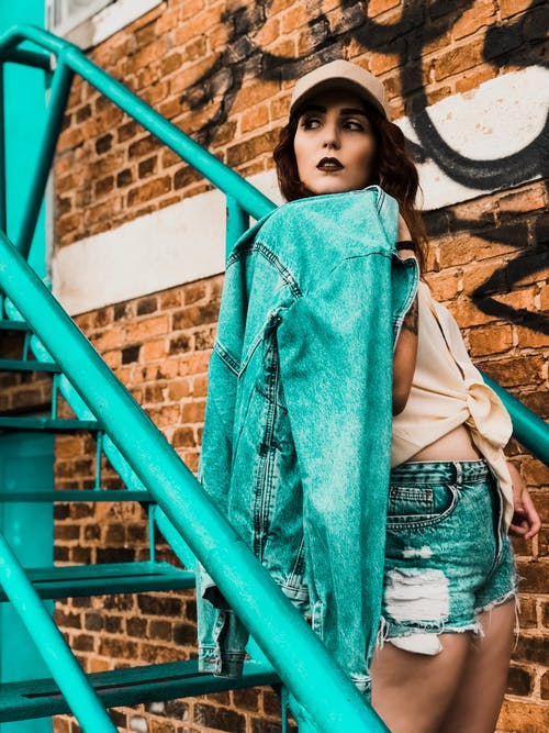 Side view of stylish ethnic lady in cap with denim jacket looking away on metal staircase near brick wall