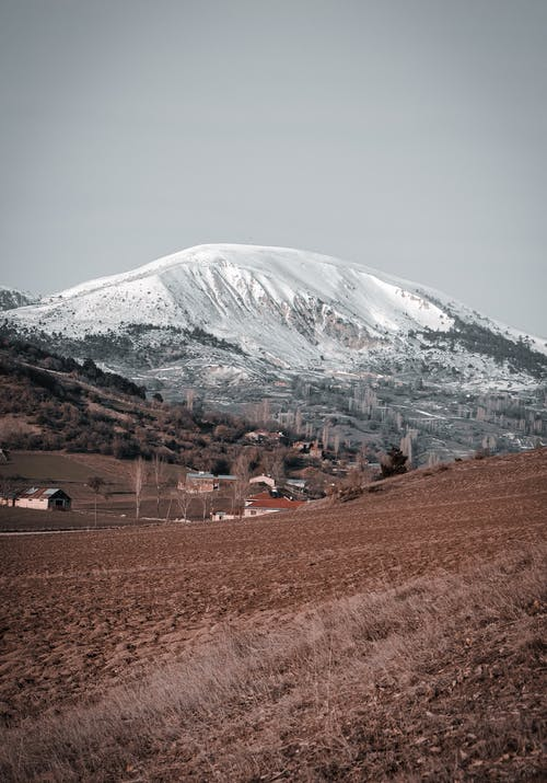 Scenery view of mount covered with snow near brown hill and houses with trees under serene sky
