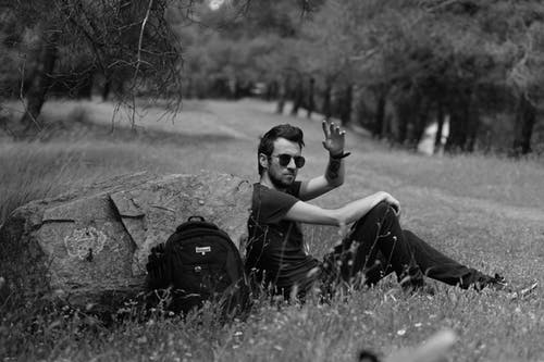 Stylish ethnic man in sunglasses resting on grass